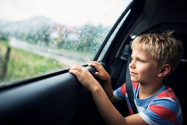 young boy looking out the car window on a rainy day